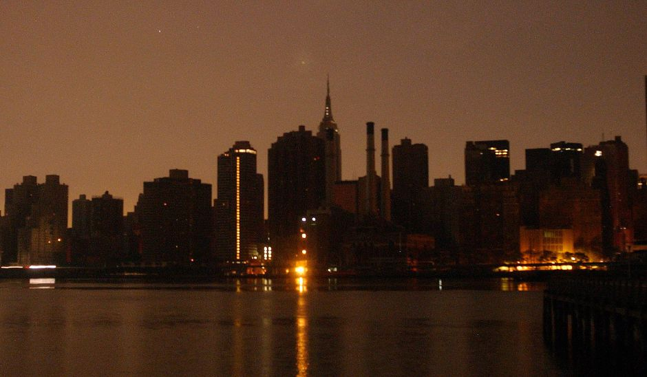 The dark Manhatten skyline, seen from Queens, is sillouetted against a pre-dawn sky Friday, Aug. 15, 2003. A widespread power outage hit most of northeastern United States Thursday afternoon, leaving the city in the dark. (AP Photos/Patricia McDonnell)
