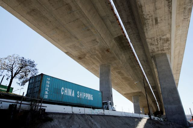 FILE- In this July 2, 2018, file photo, a truck carrying a cargo container drives under the Gerald Desmond Bridge under construction in Long Beach, Calif. China on Tuesday, Sept. 18, announced a tariff hike on 60 billion of U.S. products in response to President Donald Trump