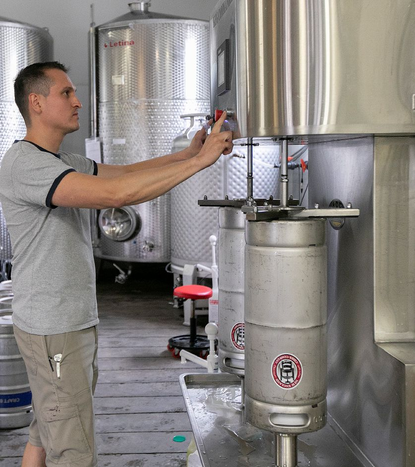 Miguel Galarraga, co-owner of New England Cider Company, cleans kegs on a keg washer at the 110 N. Plains Industrial Rd. business in Wallingford, Wed., July 17, 2019. The business is seeking to expand in its current space. Dave Zajac, Record-Journal