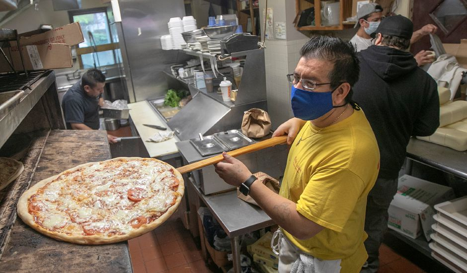 Jaime Chabla, manager, checks on a pizza at Bella Luna Pizza & Restaurant on Liberty Street in Meriden on Friday. The restaurant is now offering pizza kits. $10 for one large dough with cheese and sauce. Additional toppings are extra.