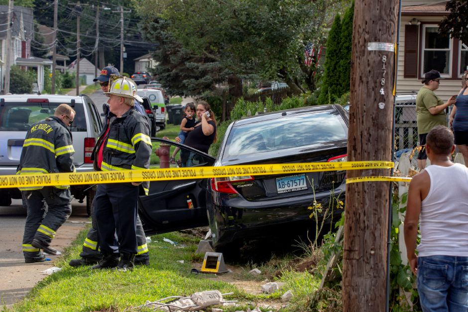 Meriden firefighters stand near a damaged car on the side of Wood Street near Summer Street after the car hit two pedestrians Aug. 30, 2019. | Richie Rathsack, Record-Journal