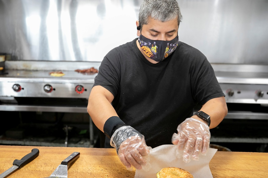 Cook George Santiago wraps up a bacon, egg and cheese bagel for a customer Monday at Fancy Bagels, 405 Queen St. in Southington. The business is celebrating 30 years. Dave Zajac, Record-Jour