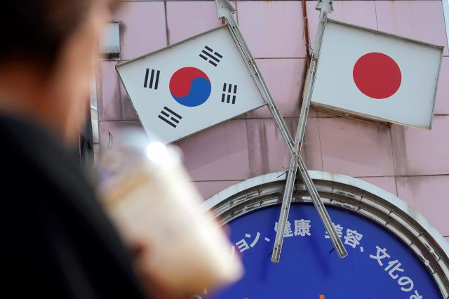 FILE - In this Aug. 2, 2019, file photo, a woman walks past an advertisement featuring Japanese and South Korean flags at a shop in Shin Okubo area in Tokyo. South Korea says it is canceling an intelligence-sharing pact with Japan amid a bitter trade dispute with its Asian neighbor. (AP Photo/Eugene Hoshiko, File)