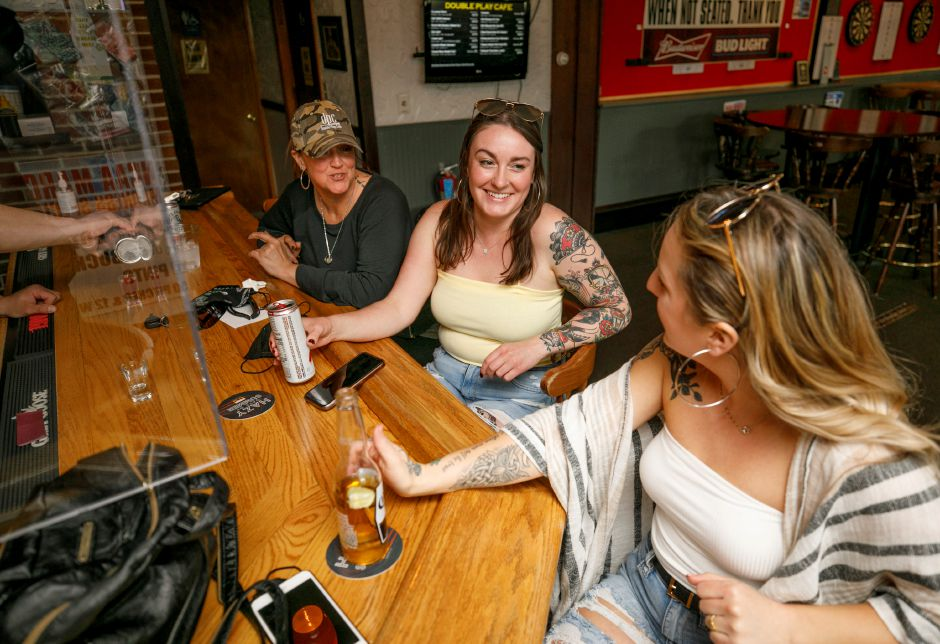 Friends, left to right, Riss Crann, of South Meriden, Rachael Kosicki, of Meriden and Nikki Calabro, of Wallingford, share in a laugh at Double Play Cafe, 320 Main St., Wallingford, Tues., Apr. 20, 2021. Local restaurants are preparing to get back to some type of normalcy after it was announced that starting next month most business restrictions are expected to lift. Dave Zajac, Record-Journal