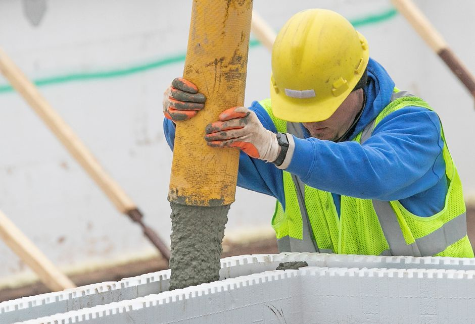 A worker pours cement into insulated concrete forms while working on the foundation of Hanover Place Veterans Housing on Hanover Street in Meriden, Mon., Jan. 13, 2020. Dave Zajac, Record-Journal