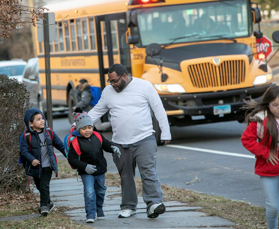 Bernard Figueroa, of Meriden, picks up son, Carmello, 5, and his son's friend, Isaiah Delvalle, 5, at their Cook Avenue bus stop in December 2018. File photo, Record-Journal