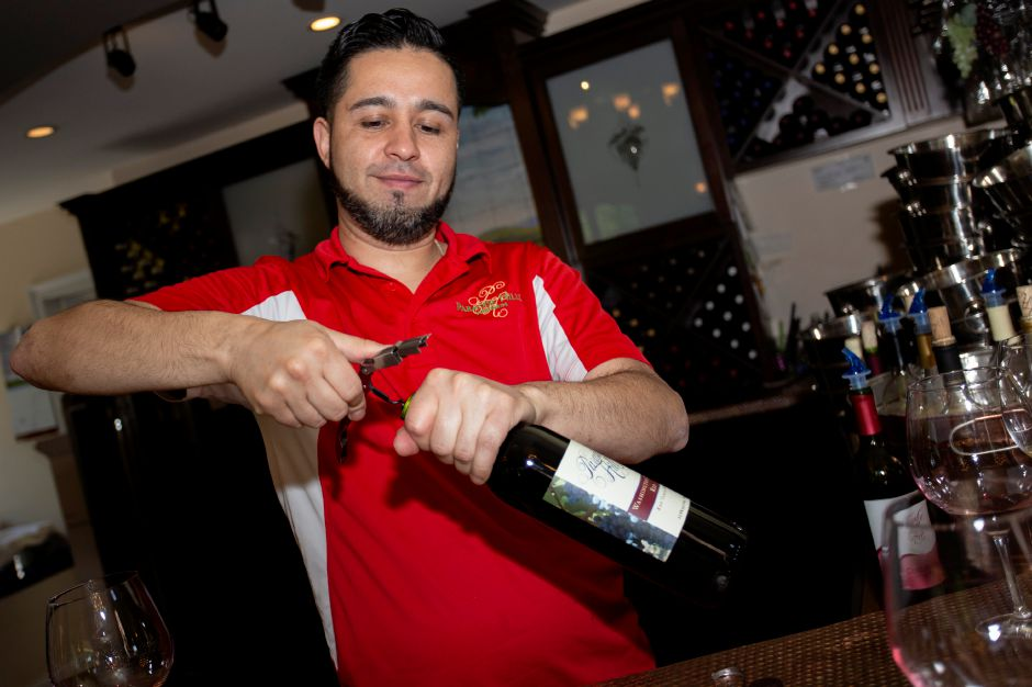 Mario Mena uncorks a fresh bottle of wine at Paradise Hills Vineyards in Wallingford May 24, 2018. | Richie Rathsack, Record-Journal