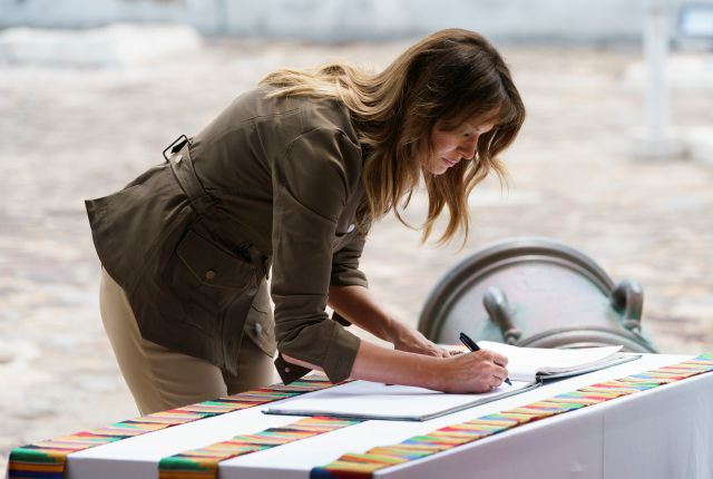 "First lady Melania Trump signs a guest book during a tour of Cape Coast Castle in Cape Coast, Ghana, Wednesday, Oct. 3, 2018. Cape Coast Castle was a ""slave castle"" used in the trans-Atlantic slave trade. Mrs. Trump is visiting Africa on her first solo international trip. (AP Photo/Carolyn Kaster)"