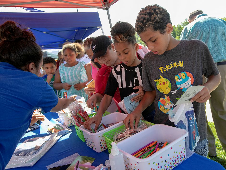 Carlos Rivera, 11, and his sister, Lileishka, 11, of Meriden, pick up school supplies and other items from the Community Healthcare Center tent during the Meriden Fire Local 1148 annual Back-to-School Expo on the Meriden Green Tuesday. Dave Zajac, Record-Journal