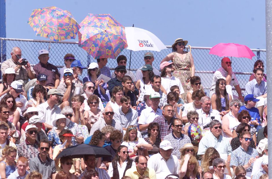 RJ file photo - The home team bleachers are full of parents at the Southington High School graduation ceremonies. Many of them used umbrellas to get out of the hot sun June 26, 1999.