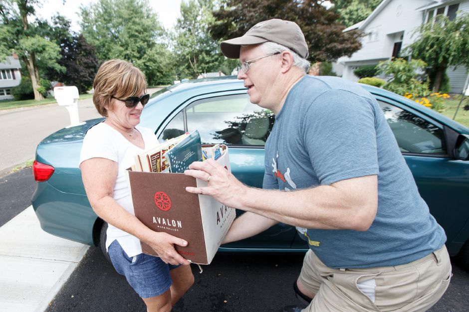 Robbin Passaro of Wallingford hands off a book donation to Jack Fitzgerald Saturday during the 6th Annual childrens book drive to benefit Read to Grow July 28, 2018 | Justin Weekes / Special to the Record-Journal