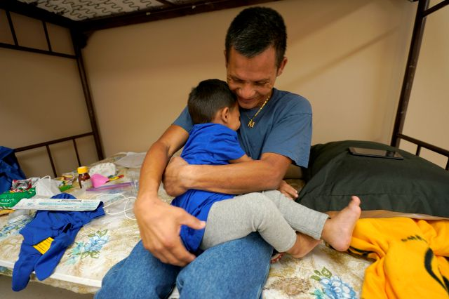 Elmer Maldonado, top, a migrant from Honduras, hugs his 1-year-old son at a shelter, Monday, March 22, 2021, in Harlingen, Texas. They spent a week in immigration custody after crossing the Rio Grande through Texas to request asylum. His experience illustrates a cycle that is repeating itself thousands of times a week amid a dramatic rise in migrant children and families at the U.S.-Mexico border: They arrive in the middle of the night by the dozens and are kept at outdoor intake sites,...