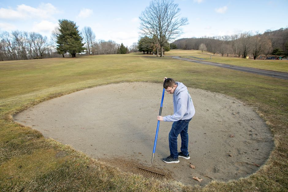 Blake Kunst, of Meriden, rakes a bunker on the 7th hole at Hunter Golf Course in Meriden, Thurs., Feb. 27, 2020. The 19-year-old diagnosed with Autism Spectrum Disorder is a maintenance worker at the course on Westfield Road. Dave Zajac, Record-Journal