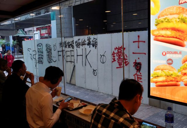 "People eat at a shop with its temporal wall painted with graffiti which reads ""Free Hong Kong"" in Hong Kong, Monday, Oct. 7, 2019. Tens of thousands of masked protesters marched defiantly in the city center Sunday, but the peaceful rallies quickly degenerated into chaos at several locations as hard-liners again lobbed gasoline bombs, started fires and trashed subway stations and China-linked banks and shops. ( AP Photo/Vincent Yu)"