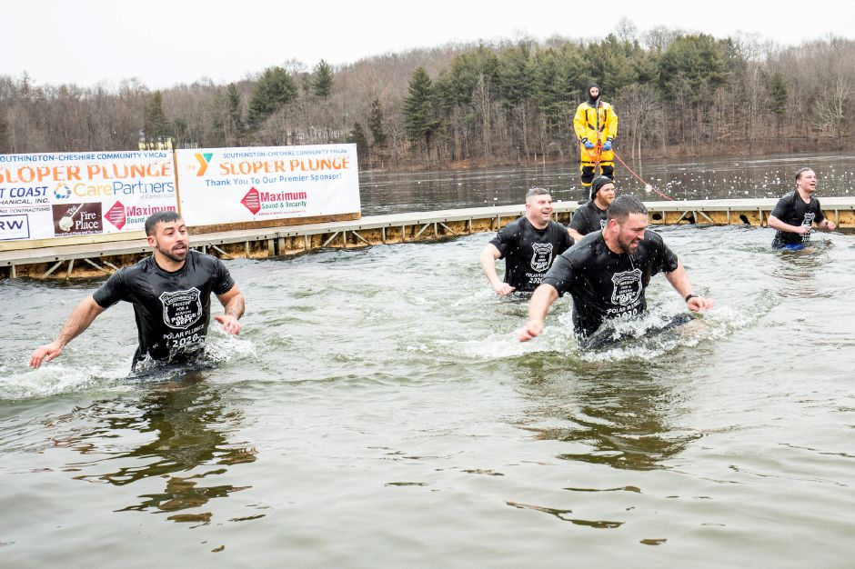 Members of Team Southington Police make a run for the beach and out of the icy waters of Sloper pond in Southington, January 18, 2020. The 15th annual Sloper Plunge by the Southington-Cheshire Community YMCAs raises money for local kids to attend camp. Photo by David Torrellas, special to the Record-Journal.