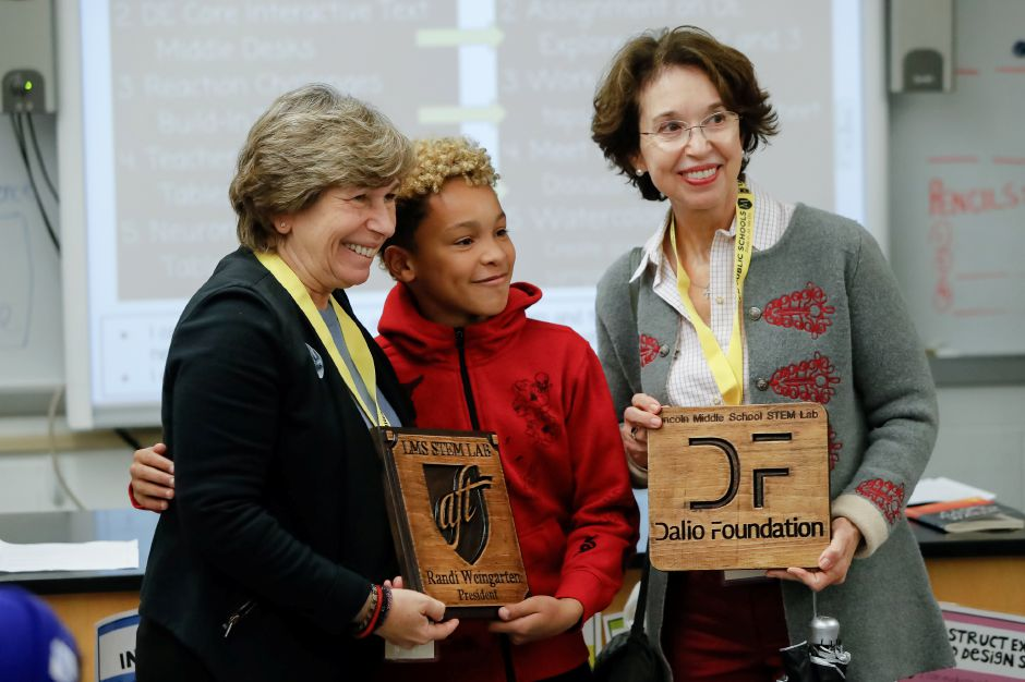 Justin Black 12 presents plaques to Randi Weingarten, president of the American Federation of Teachers left and Barbara Dalio, president of the Dalio Foundation made in the STEM class Friday at Lincoln Middle School in Meriden November 2, 2018 | Justin Weekes / Special to the Record-Journal