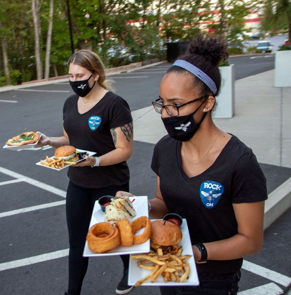 Crystal Bees Gionna Selitle left and Yanielys Vega brings out meals to a table outside during a concert at Crystal Bees in Southington on Friday, September 18, 2020. Aaron Flaum, Record-Journal