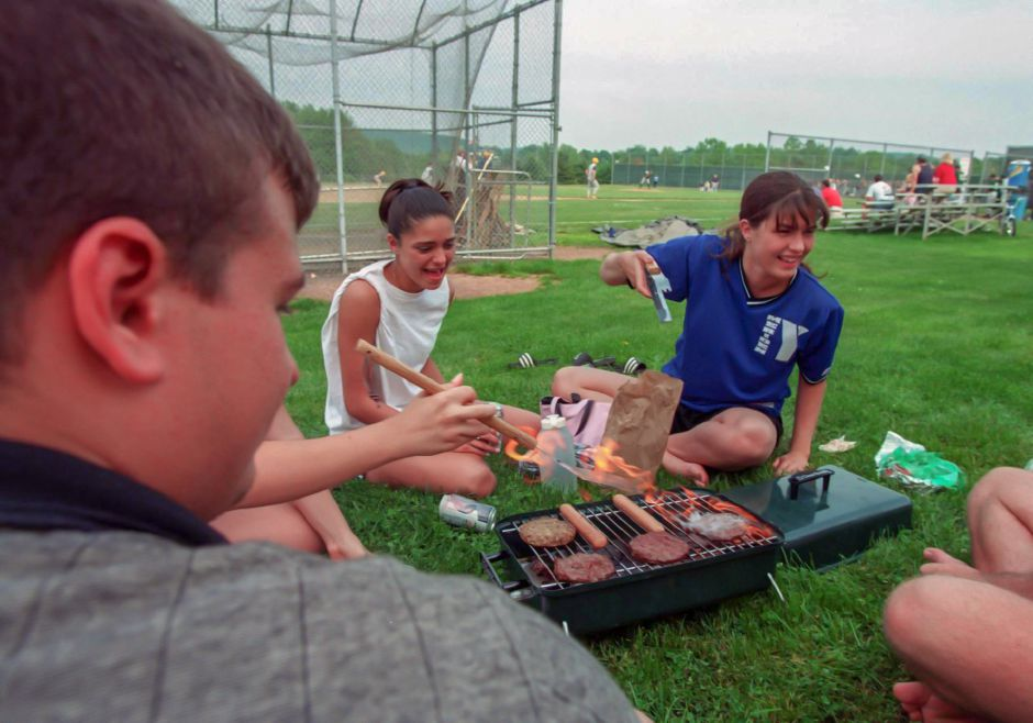 Flames shoot up from the grill as Mike Hoydilla, 18, a senior, the arm of Lisa Stellato, 18, Jen DiNoia, 17, a junrior, and Michelle Bilodeau, 18, a senior, were doing a little grilling at the Maloney Baseball game, June 1999.