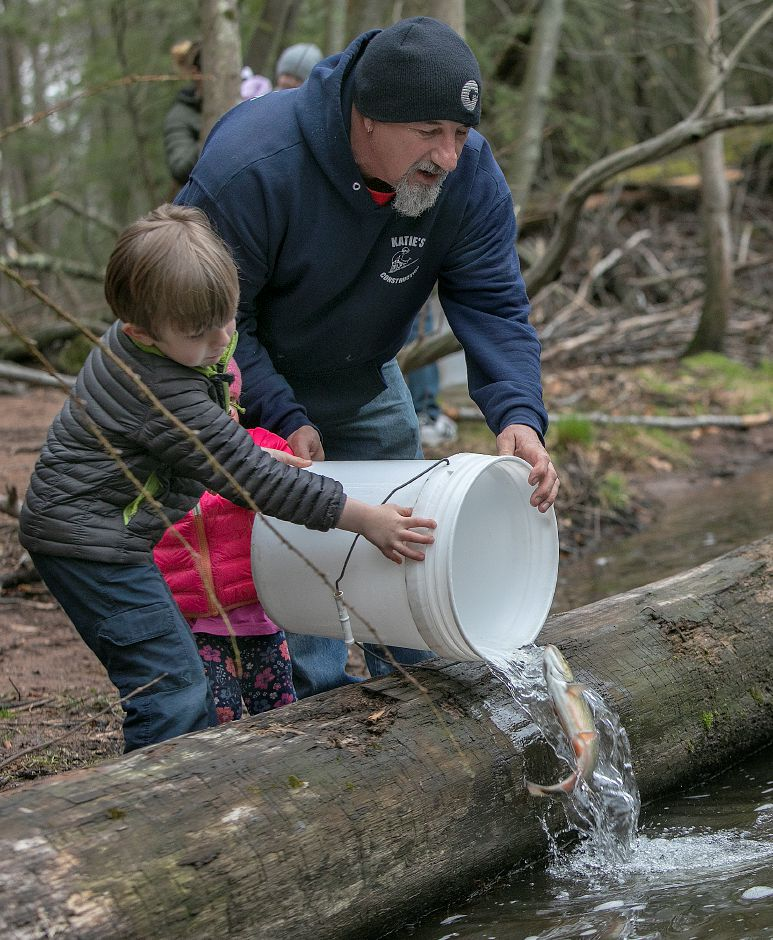 Mark Giusti, of Wallingford, and children Grayson, 4, and Charlotte, 1, release a large trout into the Quinnipiac River during the annual fish stocking along the Quinnipiac River Gorge Trail in Meriden, Mon., Apr. 8, 2019. Dave Zajac, Record-Journal
