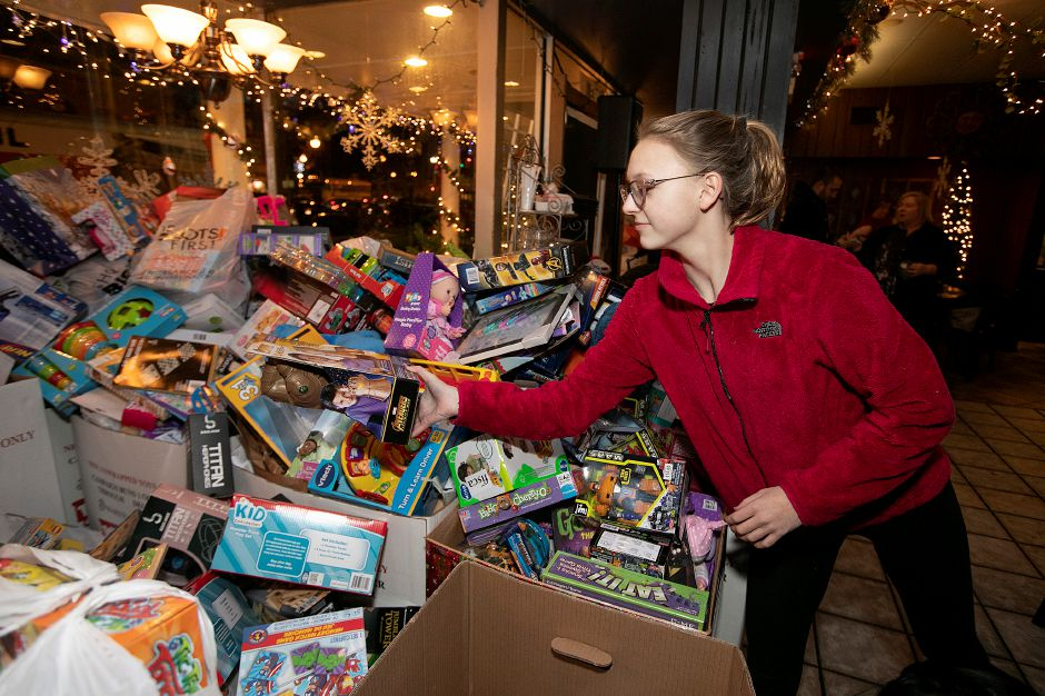 Left: Lyman Hall High School student Liliana Tangredi, 14, helps stack donated toys Thursday on a pile of thousands during the annual Toys for Tots donation event at Gaetano's Tavern on Main in Wallingford. Right: Lyman Hall volunteers Emily Chase,  left, and Makayla Cao, both 14, wear holiday hats at the event. Photos by  Dave Zajac, Record-Journal