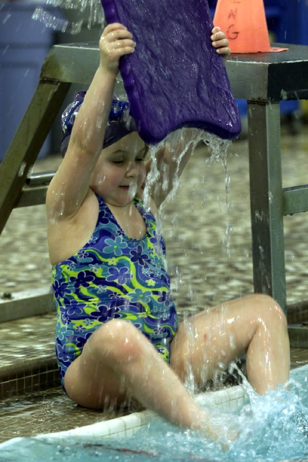 Gillian Pfeiffer,6, finds a new use for hte kick board during the Wallingford YMCA Dolphins Swim Team practice on Monday Feb. 19, 2001.