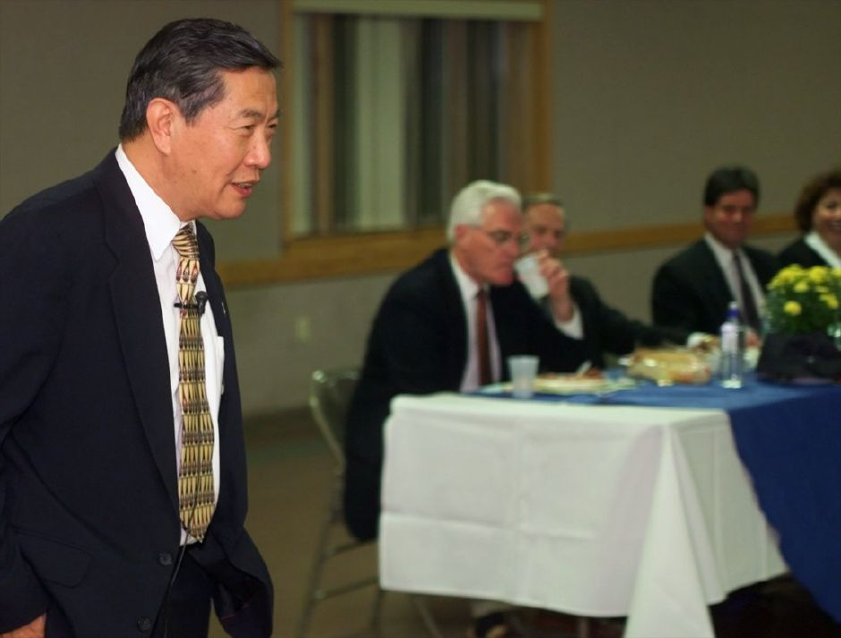 Dr. Henry Lee talks to a crowd at the Knights of Columbus Hall during a fund-raiser dinner for the Meriden Millennium Celebration committee Oct. 4, 1999. At the table to the right is Mayor Joseph J. Marrinan, Jr, Police Chief Robert Kosienski, Rep. Buddy Altobello, and Laura Gallo, from l-r