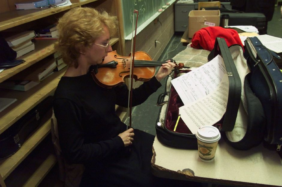 First violinist Anna Lasley, of Farmington, warms up in the music room of Maloney High before the start of the 52nd season opener for the Meriden Symphony Orchestra Sat., Sept. 25 1999.