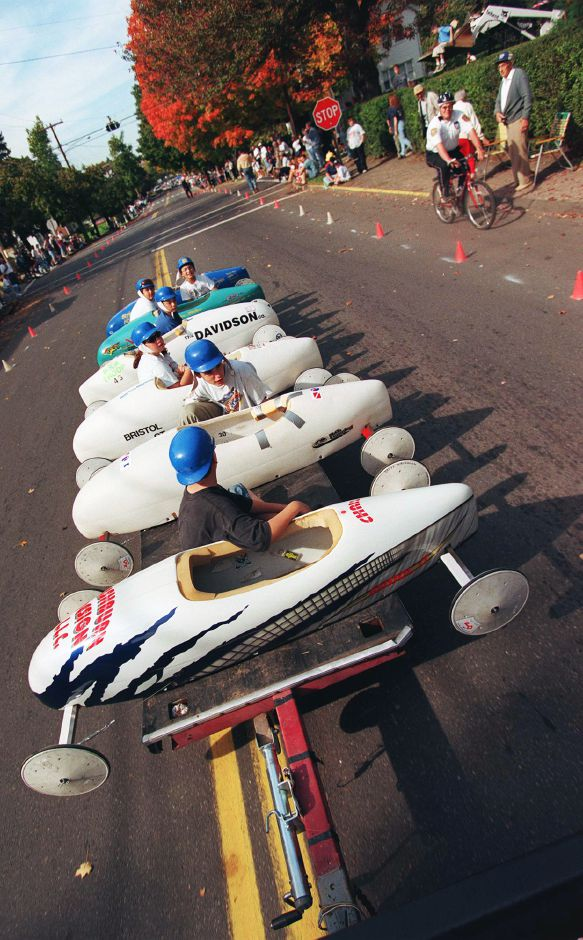 Racers are pulled uphill by a pickup truck to the starting line of Sunday