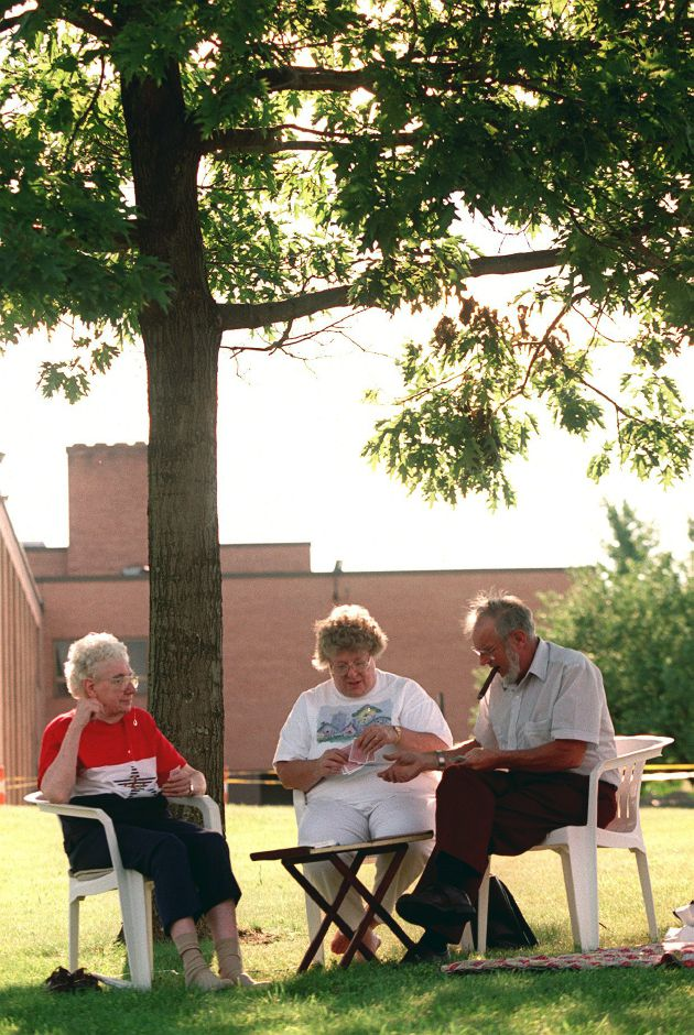 Shirley Mose, left, of Meriden, plays cards with her daughter Kathy Ayers, middle, and son-in-law Royal Ayers, right, under a tree in front of Sheehan High School in Wallingford several hours before the fireworks show Saturday night July 1, 2000.