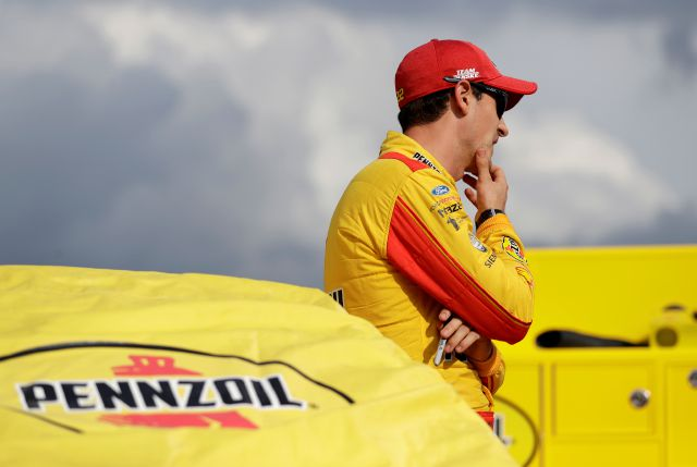 Joey Logano waits by his car before qualifying for a NASCAR Cup Series auto race at Charlotte Motor Speedway in Concord, N.C., Friday, Sept. 28, 2018. (AP Photo/Chuck Burton)