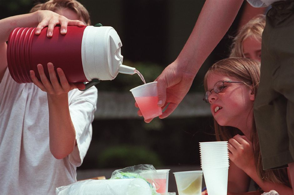 Jane Smithwick, 8, keeps a watchful eye as her brother Ben Smithwick, 11, pours lemonade for a customer at their makeshift lemonade stand at their home on Maplewood Avenue in Wallingford July 3, 2000. The Smithwick