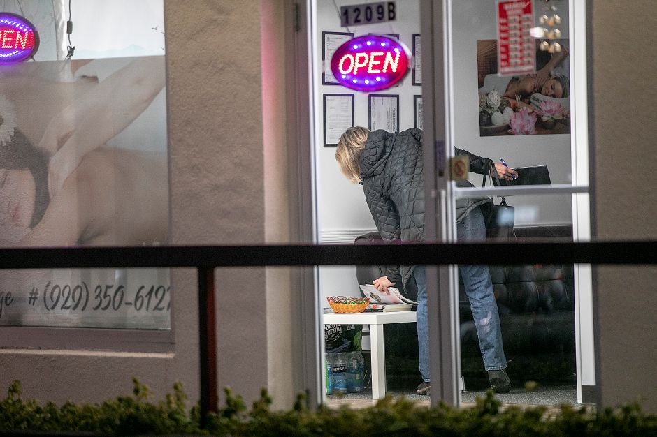An investigator from the State of Connecticut Department of Labor Wage & Workplace Standards Division looks over materials after closing down Exquisite Massage at 1209B South Broad St. in Wallingford, Thurs., Jan. 30, 2020. Dave Zajac, Record-Journal