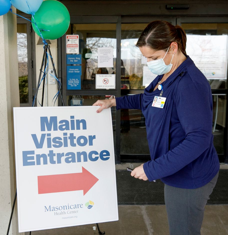 Long Term Care Administrator Courtney Wood places a sign at the entrance to Masonicare Health Center Wallingford, Wed., Mar. 10, 2021. Masonicare Health Center opened to visitors Wednesday afternoon. Dave Zajac, Record-Journal