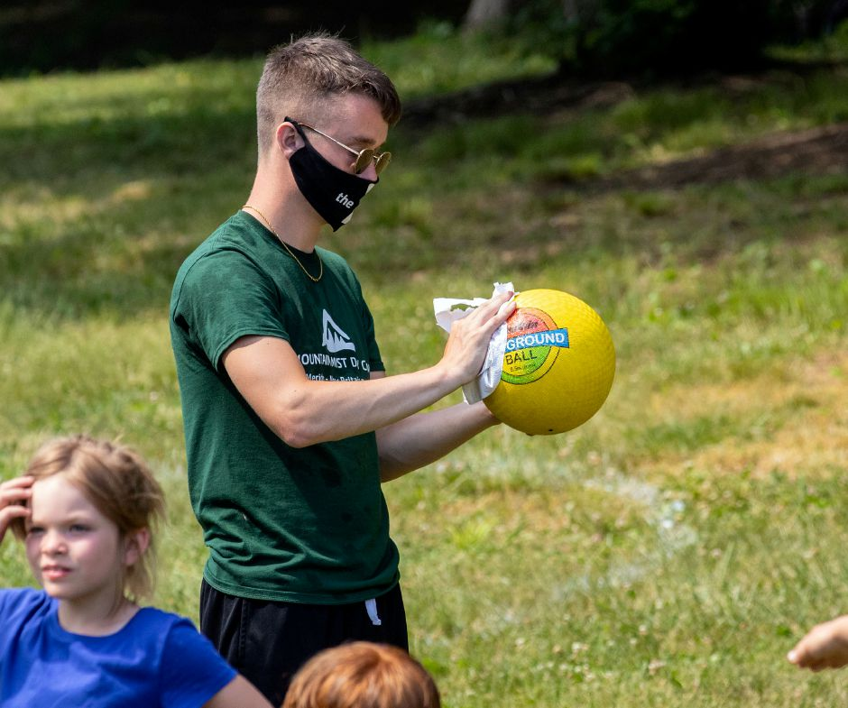 Camp counselor Bryan Brazeo disinfects the ball between innings of a kickball game during camp at the Meriden YMCA's Mountain Mist Day Camp on Friday, June 26, 2020. Each group has their own sports equipment and cleaning supplies that they use to disinfect the equipment. Aaron Flaum, Record-Journal