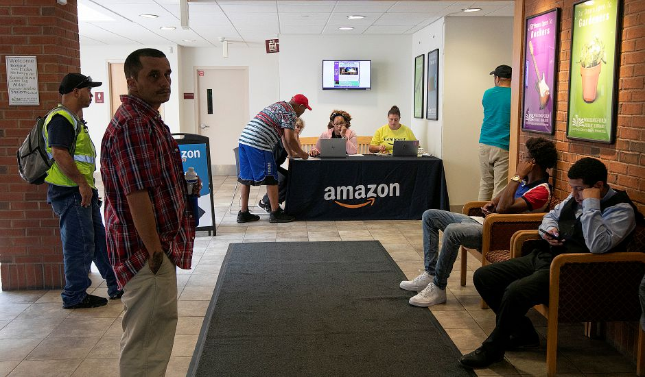 Job candidates check in and wait for an Amazon presentation during a hiring event at the Wallingford Public Library, Wed., July 17, 2019. Dozens of people attended the Amazon hiring event held in the Community Room and lobby of the library. Dave Zajac, Record-Journal