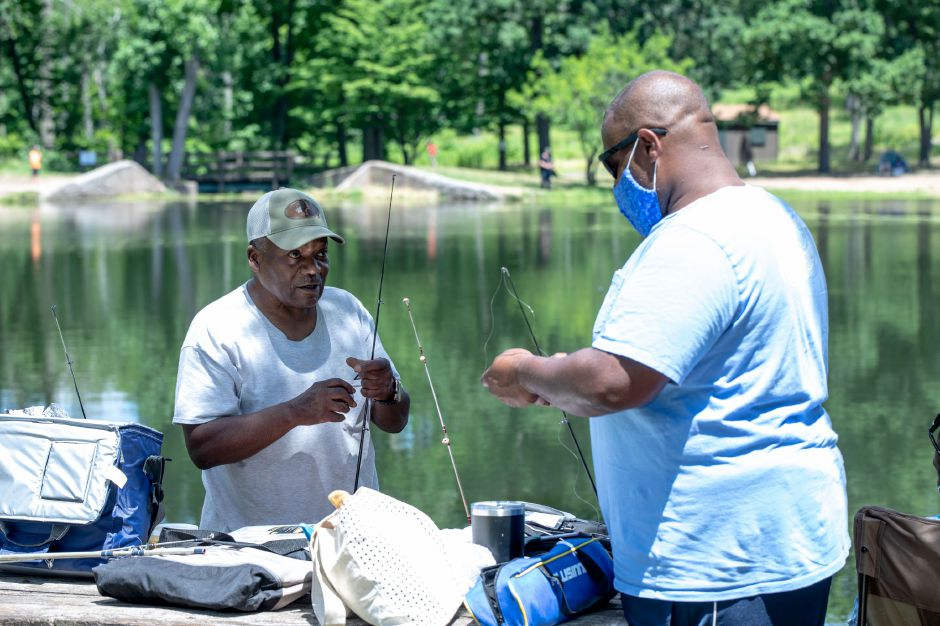 Phillip Dozier Sr. speaks with his son, Phillip Dozier Jr., while preparing fishing reels at Wharton Brook State Park in North Haven, Connecticut on July 12, 2020. While Dozier Sr. said he virus remains a concern, he felt comfortable at the park since other visitors were being respectful of social distancing rules. | Devin Leith-Yessian/Record-Journal