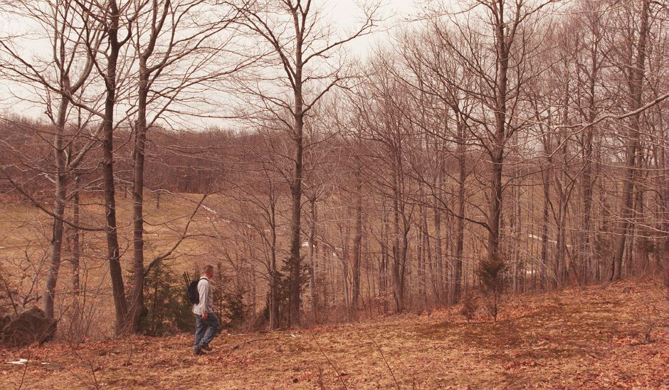RJ file photo - Tom Pepe of Meriden hikes above a hillside in Meriden on land populated by coyotes, March 1999.