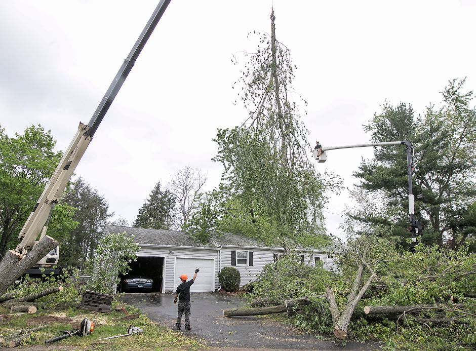 Crews work to clear a large tree that fell on a residence at 103 Pond Hill Rd. in Wallingford during Tuesday
