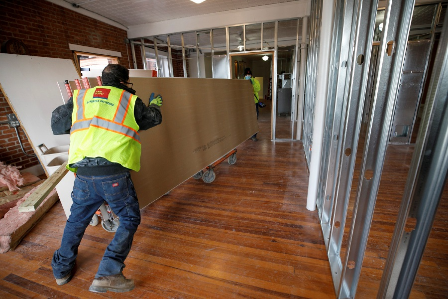 Workers for North Haven-based L&W Supply maneuver a cart of drywall Thursday while renovating a large space over Gaetano
