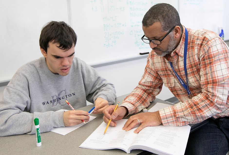 Math professor Mohamed Mountassir, right, goes over a few graphs with Alex Cable in March.