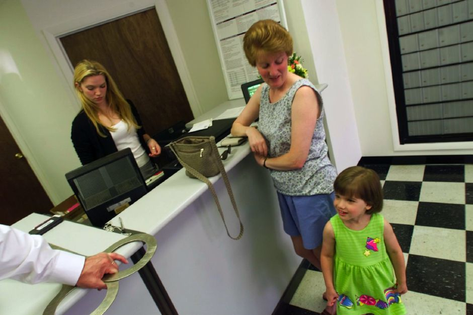 Katelyn Gullo,4 and her mom Maureen Gullo chats with Mayor Joe Marinan ( hand on left) as Christina McFadzen waits on them at the new customer postal unit at Shipping and Business Center of Meriden, June 1999