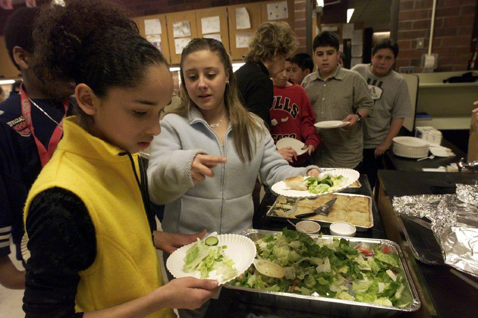 Lydben Castillo, left, looks over a spread of Greek foods with classmate Jackie Barse, right, during Washington Middle School