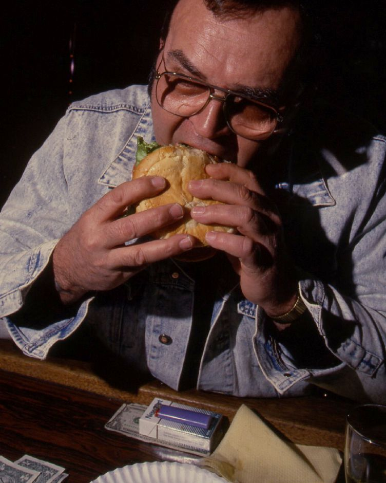 RJ file photo - Paul Lemart bites into a man-size burger during lunch at DeLuco