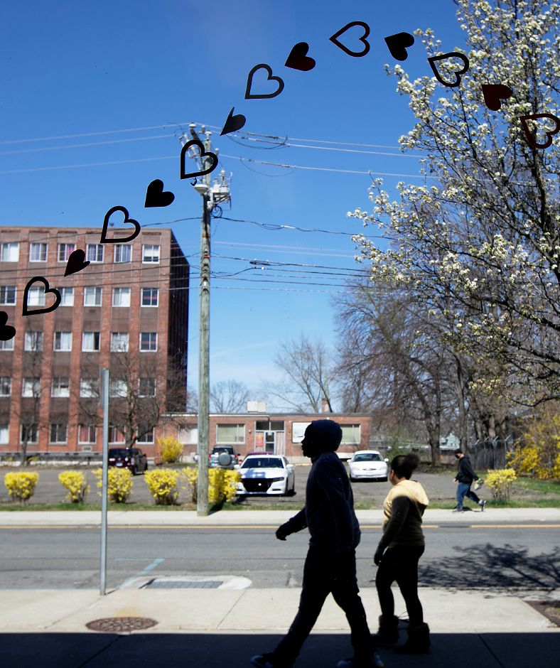 "Pedestrians walk by hearts on the front windows of the Meriden Public Library, Mon., Apr. 6, 2020. The library is inviting others to join in the worldwide initiative of putting hearts in windows with a ""Spread Love Not Germs"" theme. Dave Zajac, Record-Journal"