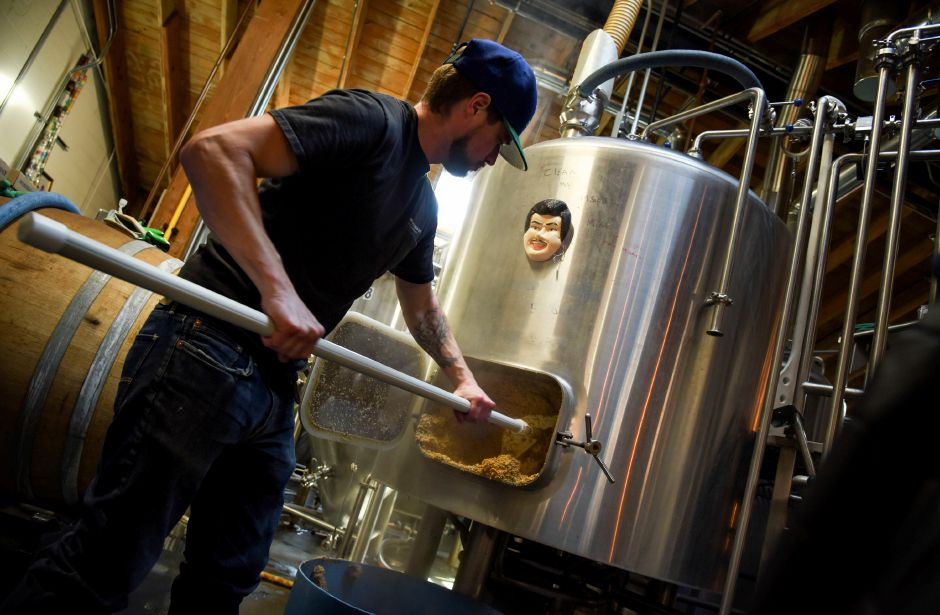 Brewer Mike Wilkie removes used grain from a mush tun at Kinsmen Brewing Co. in Southington on Jan. 15, 2020. The grain is then used by a local farmer to feed livestock. | Bailey Wright, Record-Journal