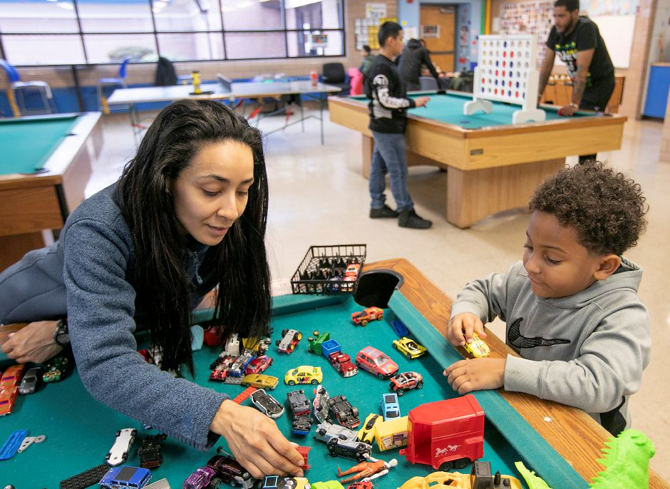 Rosie Martinez, recreation program specialist, helps Jakeem Nelson, 5, pick out cars for racing at the Boys and Girls Club in Meriden.