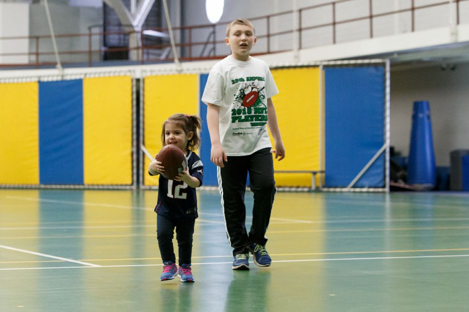 Violet Sheren, 2, of Wallingford, and cousin Nick Morello, 9, of Meriden, play with the football Saturday during the United Way NFL weekend kids camp at Choate Rosemary Hall in Wallingford. Photos by Justin Weekes, Special to the Record-Journal
