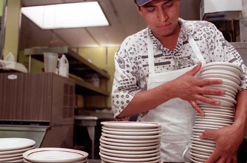 During breakfast hours dishwasher Alfredo Billafon of Wallingford, stacks clean plates after washing them in the kitchen of the Neptune House June 29, 2000.