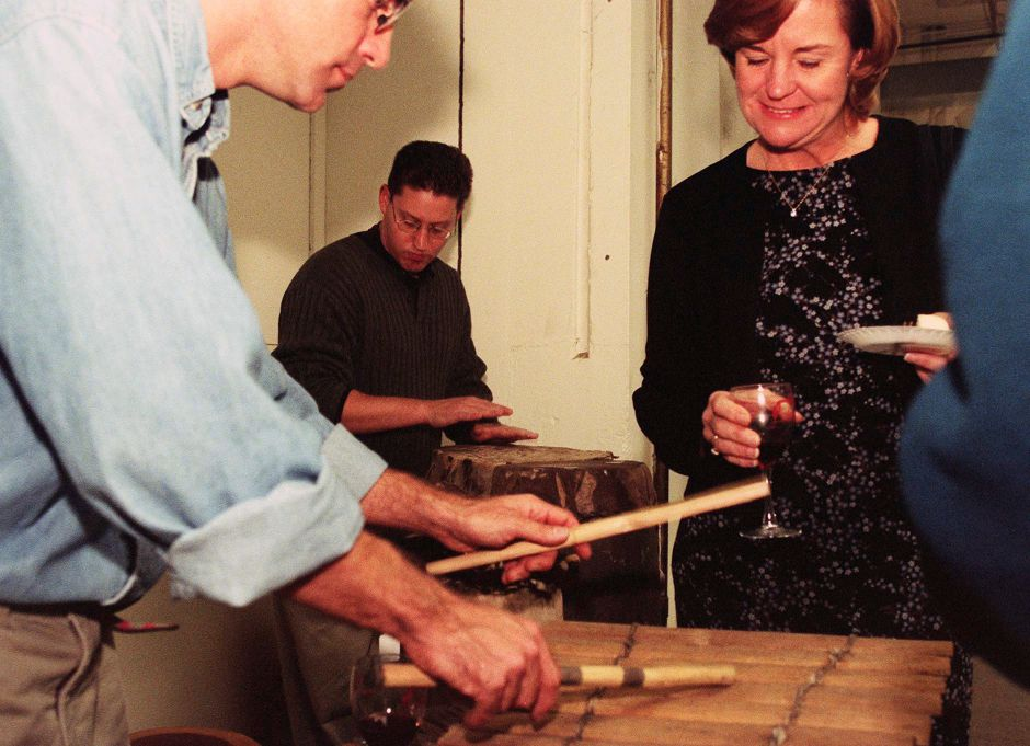 YWCA fundraiser at Shona Gallery in Meriden. (L) Craig Norton shows Kathy Russo of Branford some of the African drums Oct. 22, 1999.