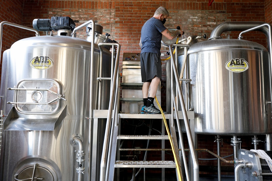 Brewery Manager Robert Todd rinses down a kettle at Witchdoctor Brewing Company on Tuesday.